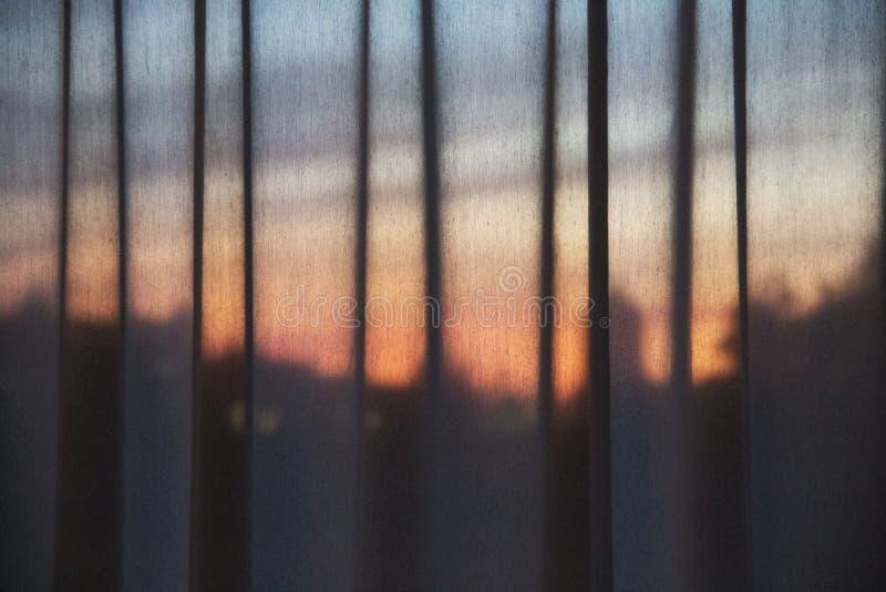 Solnedgång till och med en gardin royaltyfri bild