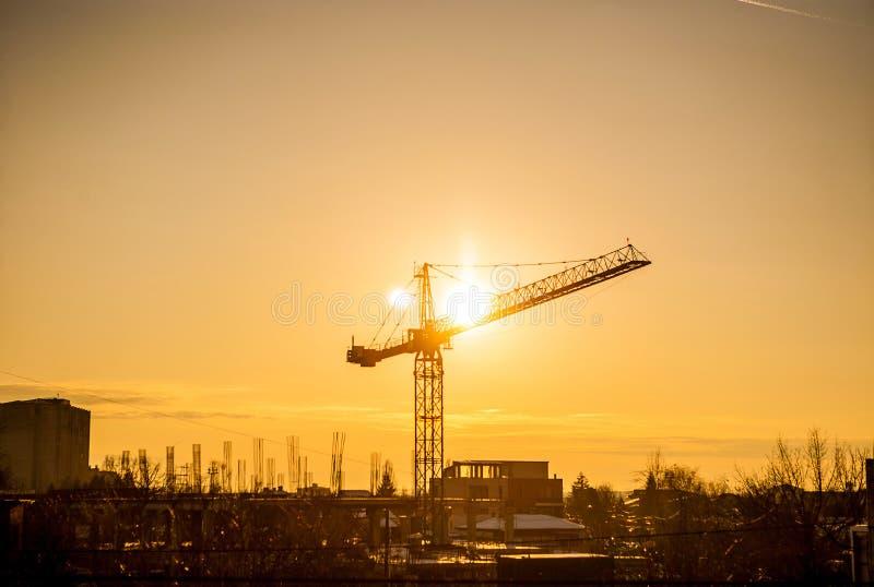 Solnedgång till och med en kran i industrialiserat område av staden royaltyfria foton