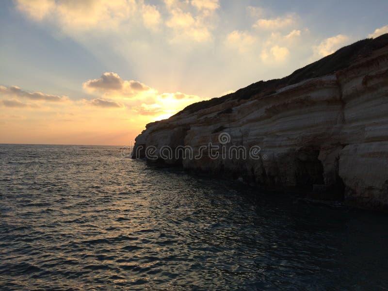 Solnedgång under den molniga kusten och havet arkivbild