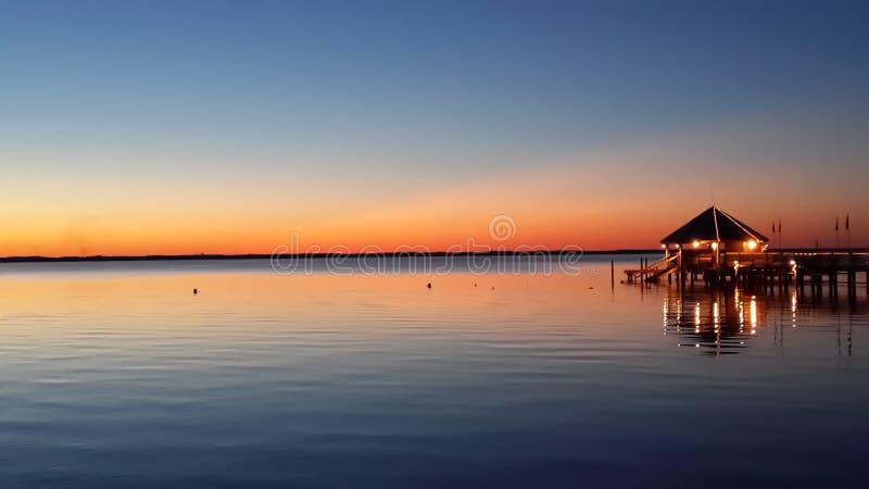 Solnedgång, vatten och en röd himmel royaltyfria bilder