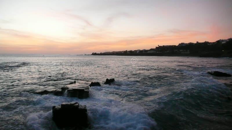 Solnedgången över Atlanticet Ocean med vaggar i förgrunden arkivfoton