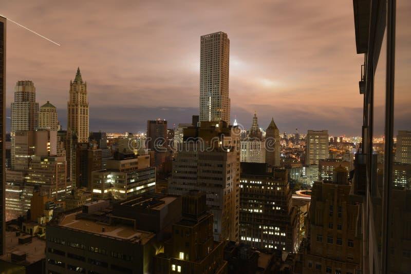 Solnedgången över ett mörker Manhattan postar sandigt arkivbild