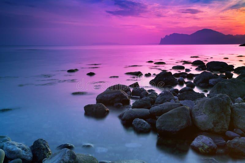 Solnedgången över ett stenigt seglar utmed kusten arkivfoto