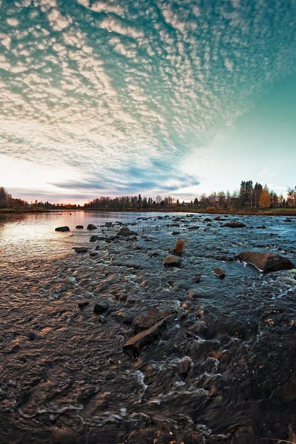 Solnedgången över floden vaggar arkivbilder
