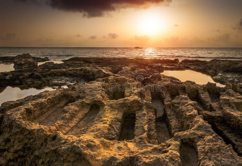 Solnedgången över havet och den steniga kusten med forntida fördärvar arkivfoto