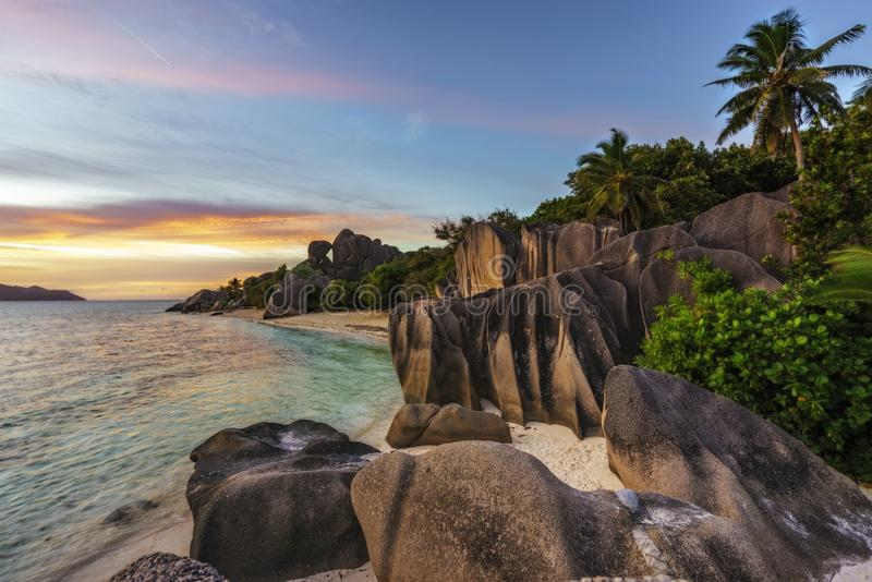 Solnedgången över vaggar, sandpapprar, gömma i handflatan, turkosvatten på tropisk strand, l royaltyfri fotografi