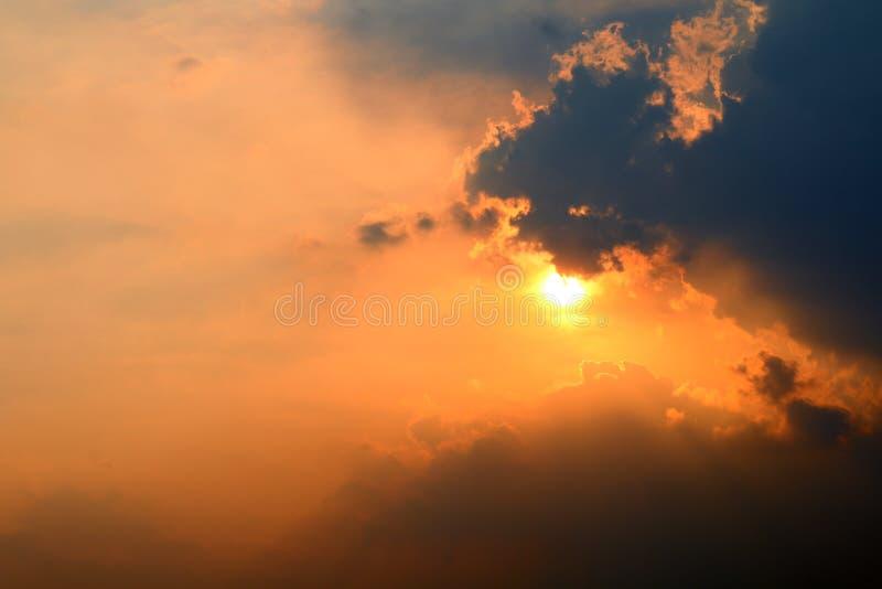 Solnedgången den orange himmelsolen ställer in över molnmörker, den guld- himmelsolen gör ljusare molnafton fotografering för bildbyråer
