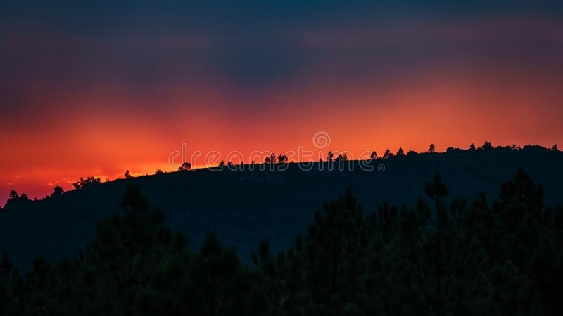 Solnedgången efter bergen, som brand flammar royaltyfri bild