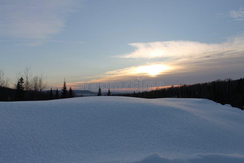 Solnedgången eller soluppgången på horisonten med överkanten av berget och skogen royaltyfria foton