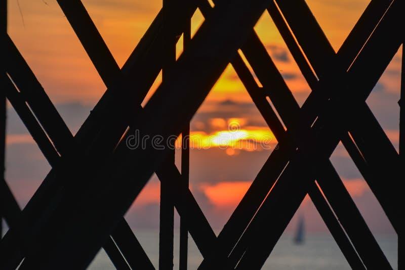 Solnedgången färgar som sedda igenom balkar av fiskepir arkivfoto