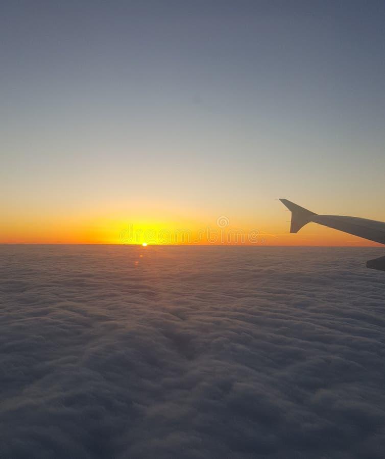 Solnedgången fördunklar flygplansikt royaltyfria foton