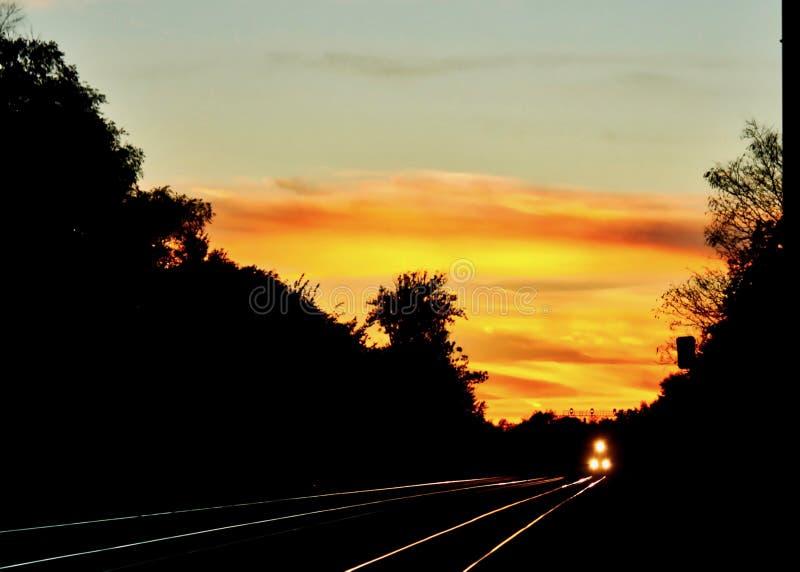 Solnedgången glöder på stängerna av ett järnvägspår i Chicago förorter, som drevet att närma sig, billyktor som skiner arkivfoton