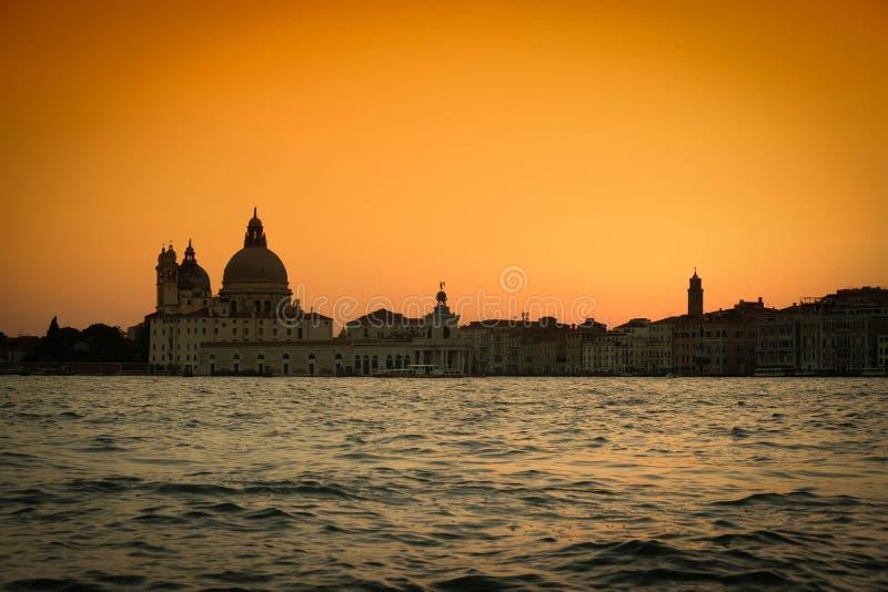 Solnedgången i Venedig framme av kyrkan av hälsa arkivfoton