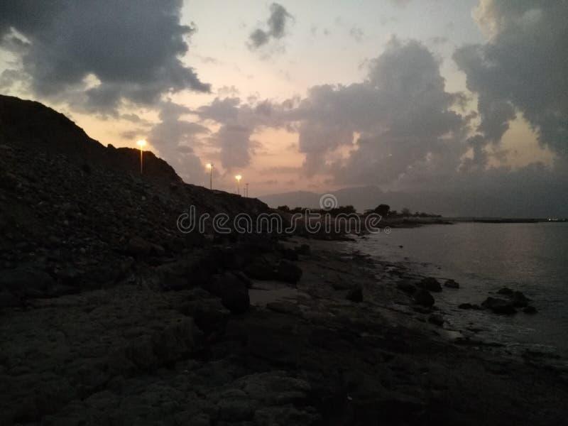 Solnedgången ljuset försvinner i stranden royaltyfri bild