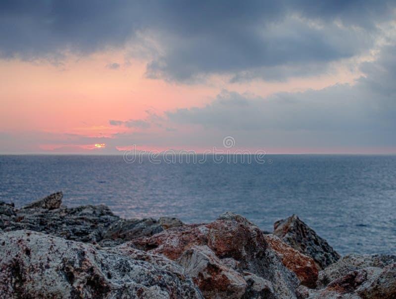 Solnedg?ngen med rosa och bl?a moln ?ver en lugna medelhav mot texturerat grovt kust- vaggar i menorca arkivfoto