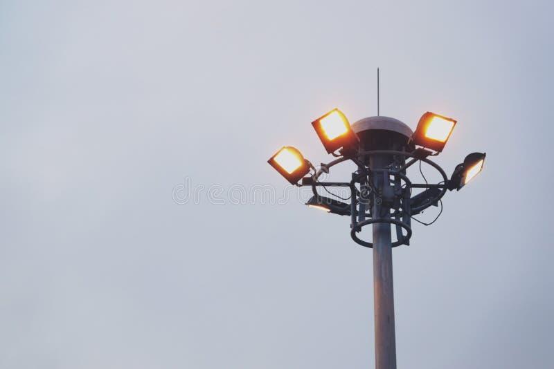 Solnedgången och den högväxta masten med flodljus på sportar parkerar royaltyfri foto