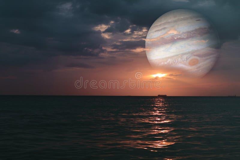 solnedgången och jupiter på horisontalhavsvatten ytbehandlar färgrik clou arkivfoto