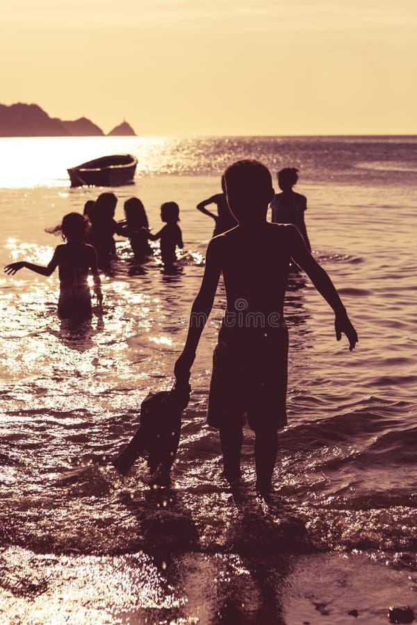 Solnedgången och konturn av barn med havet och stranden beskådar, märker arkivbilder