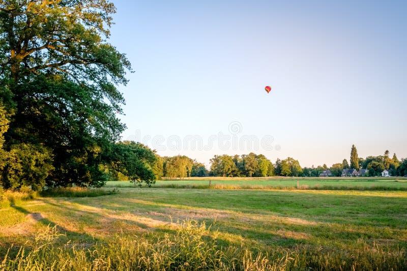 Solnedgången och luftballongen ovanför holländaresommar landskap Delden, Twente arkivbilder