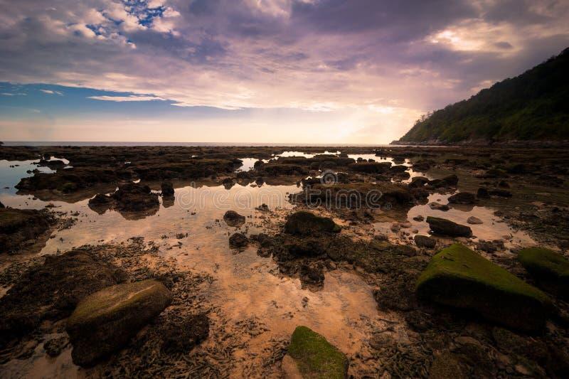Solnedgången på den tropiska stranden med vaggar och stenar fotografering för bildbyråer