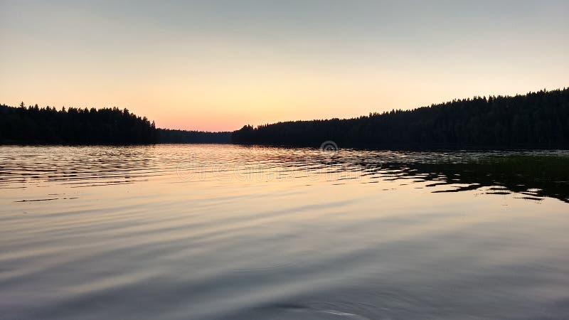 Solnedgången på en sjö som är ljus - blåa och rosa färger som reflekterar på vattnet royaltyfri fotografi