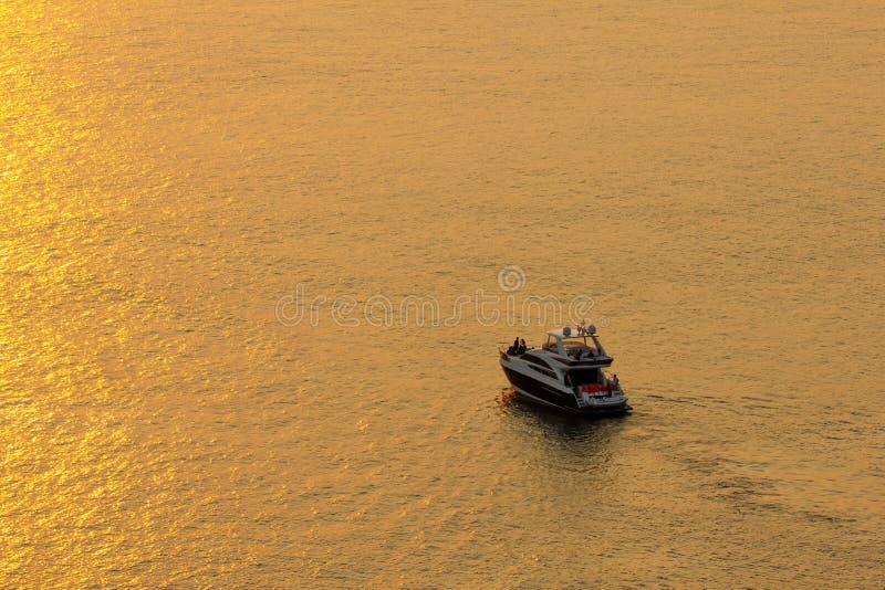 Solnedgången på havsyttersidan reflekterar solen i guld turisten parkerar fartyget för att se skönheten av solen arkivbilder