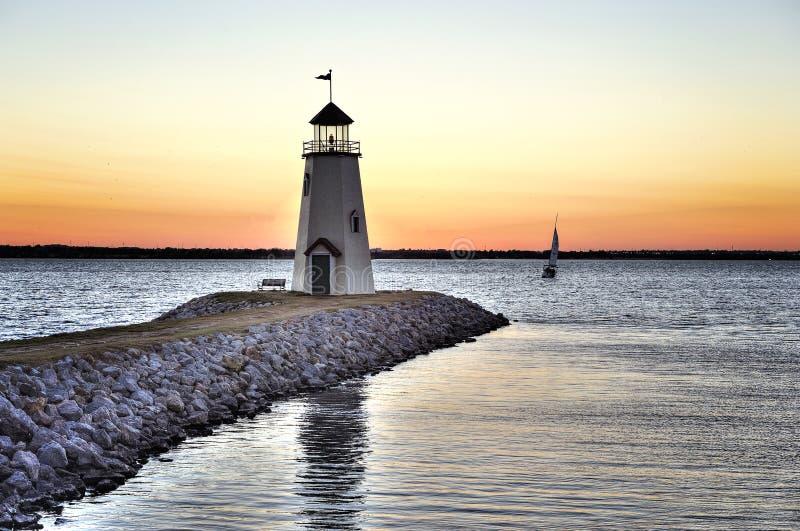 Solnedgången på sjön Hefner i Oklahoma City, fyren i förgrunden och ett ensamt seglar fartyget på vattnet royaltyfri fotografi