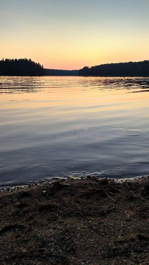 Solnedgången på sjön i färger av ljus - som är blått som är orange och som är rosa arkivfoto