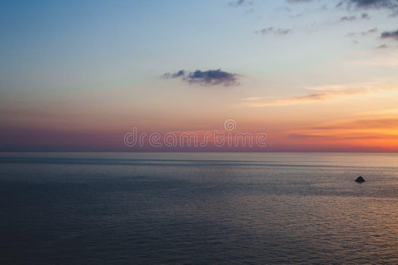 Solnedgången på stranden med något fördunklar i himlen Blåa och rosa skuggor med mörka moln placera sig quiet Avslappnande plats  royaltyfri foto