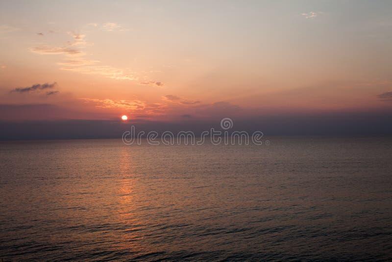 Solnedgången på stranden med något fördunklar i himlen Blåa och rosa skuggor med mörka moln placera sig quiet Avslappnande plats  arkivbilder