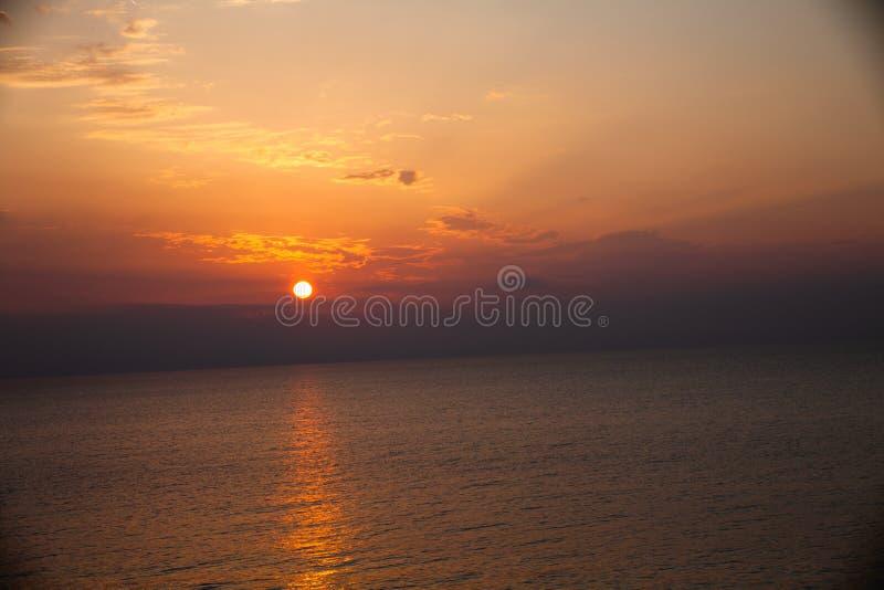 Solnedgången på stranden med något fördunklar i himlen Blåa och rosa skuggor med mörka moln placera sig quiet Avslappnande plats  royaltyfria bilder