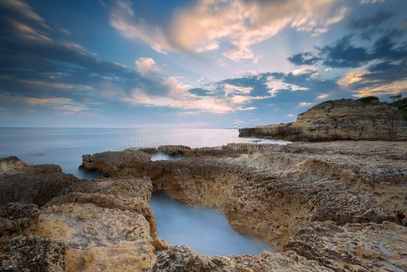 Solnedgången på strandpraiaen gör Evaristo nära Albufeira med en lång exponering fotografering för bildbyråer
