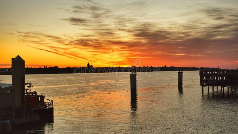 Solnedgången reflekterade av vattnet royaltyfri bild