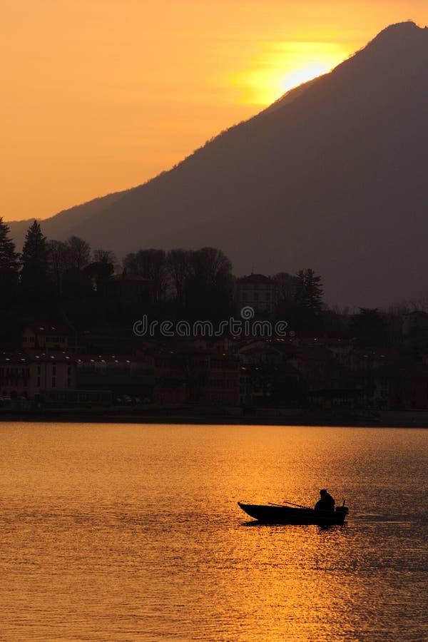 Solnedgången reflekterade in i sjön gammal fiskare på arbete royaltyfri foto