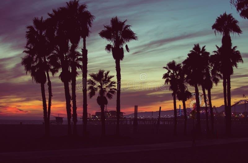 Solnedgångfärger med gömma i handflatan konturer i Santa Monica arkivfoto