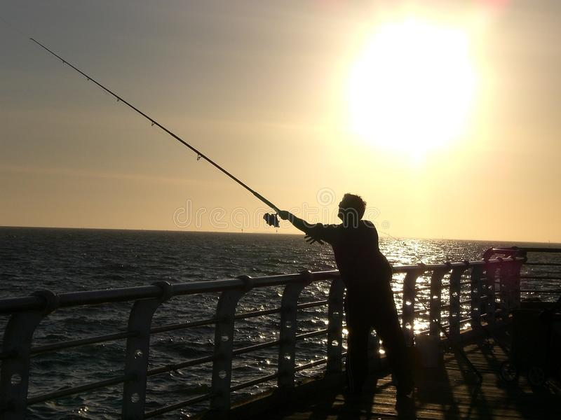 Solnedgångfiske på pir royaltyfri bild