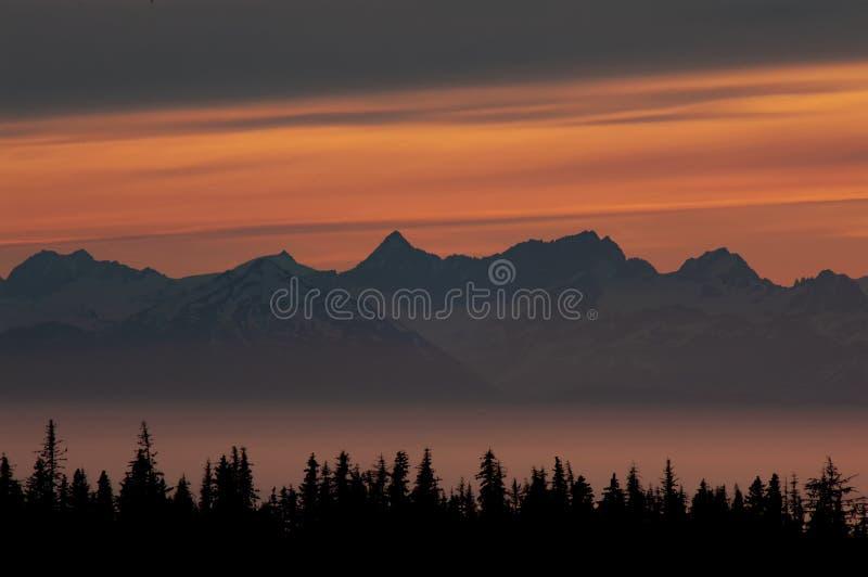 Solnedgångglöd över bergmaxima i en dimmig fjärd royaltyfri foto