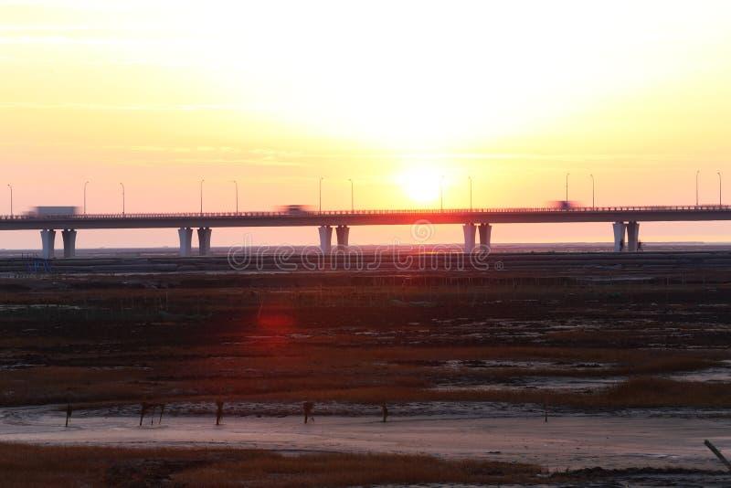 Solnedgångglödet, världens längsta bro har medel i trafik royaltyfria bilder