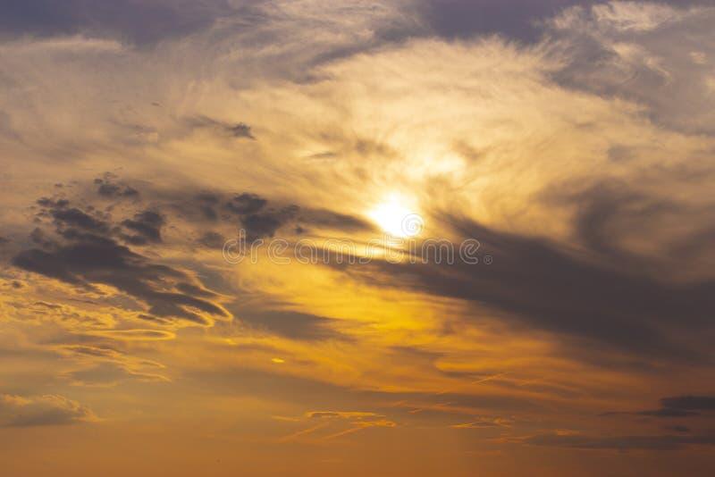 Solnedgånghimlen, solen i den orange himlen döljer bak mörkt - blåa moln Härlig himmel på solnedgången, bakgrundstapet arkivbild