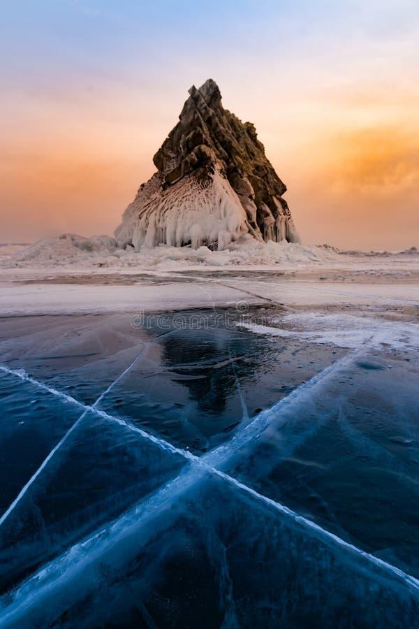 Solnedgånghimmel över den djupfrysta vattensjön och stenen, Baikal Ryssland vintersäsong royaltyfria bilder