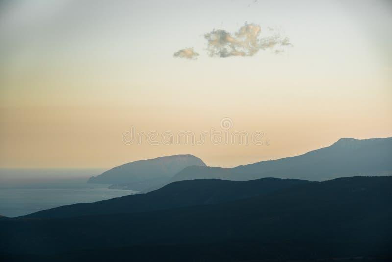 Solnedgånghimmel över kullar och havet royaltyfria bilder