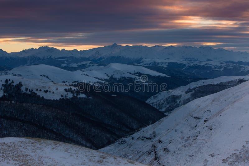 Solnedgånghimmel i molnen över bergen som täckas med snö arkivfoton