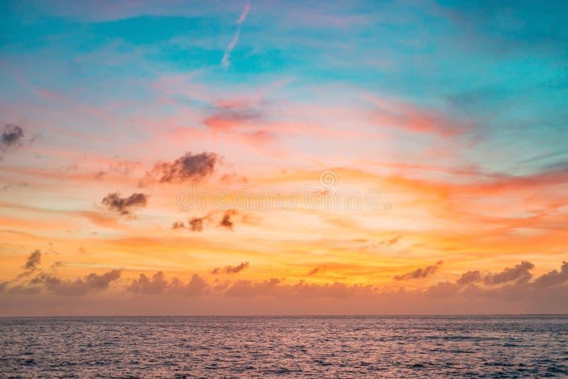 Solnedgånghimmel i röd och blå färg med subtila moln över havshorisonten royaltyfria bilder