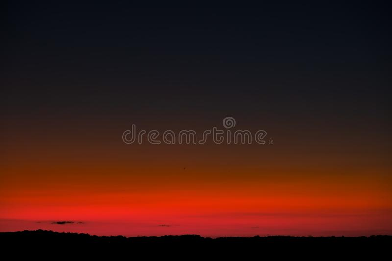 Solnedgånghimmel med den ljusa röda horisonten och halvmånformigmånen arkivbild