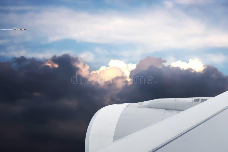 Solnedgånghimmel med stormmoln och ett annat flygplan flyga iväg arkivbild