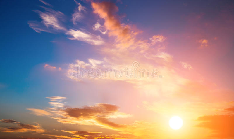 Solnedgånghimmel och sol. Dramatisk solnedgånghimmel med apelsinen färgade moln och solen. royaltyfri foto