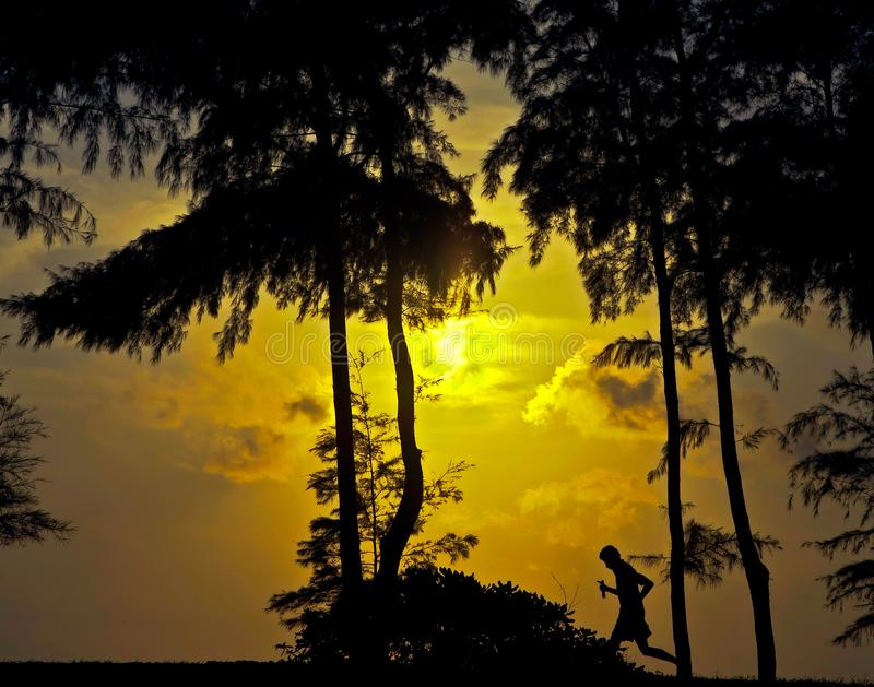 SolnedgångJogger på stranden i Thialand arkivfoton