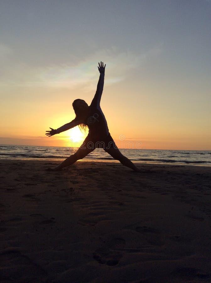Solnedgångkontur av en ung flicka arkivfoto