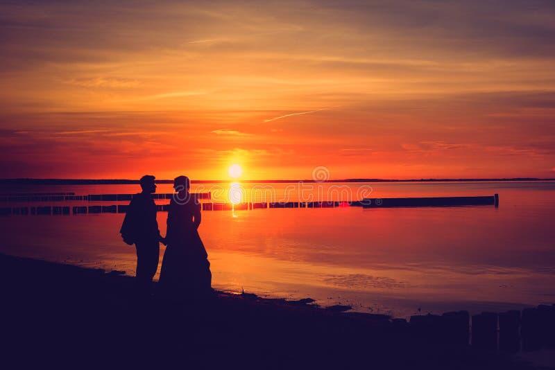 Solnedgångkontur av ett gifta sig par på stranden royaltyfri bild