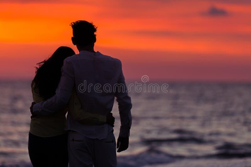 Solnedgångkonturn av barn kopplar ihop förälskat krama på stranden arkivfoto